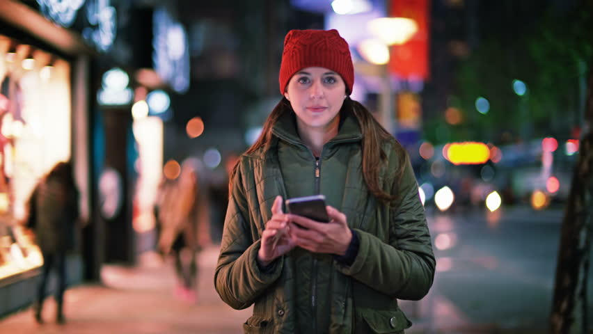 Attractive and cheerful young woman using smartphone in a crowded street. She is checking mails, chats or the news online while walking. City at night.