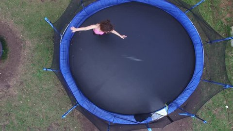 Woman in sports suit jumps and rotates on round trampoline. Aerial view
