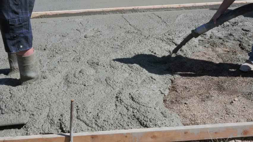 Men Pour And Level A Concrete Patio On A Job Site   4K Stock Footage Clip
