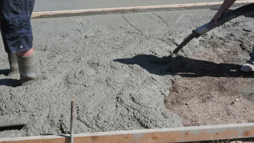 Men Pour And Level A Concrete Patio On A Job Site   4K Stock Video Clip
