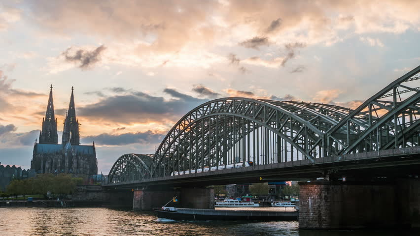 Sunset timelapse of Cologne Cathedral and Hohenzollern Bridge, Germany. Video with moving clouds, sunset lights, and night illumination.