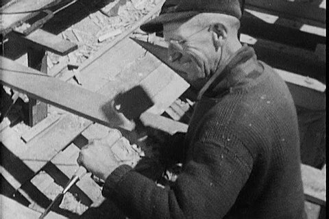 Men work tirelessly to finish off the construction of a wooden fishing boat in the town of Essex, Massachusetts, documented in a film from the 1940s. (1940s)
