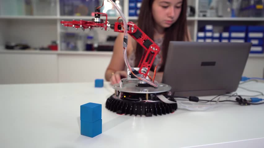 Experiment with intelligent manipulator. industrial robot model. Robot with optical recognition system, School girl in robotics laboratory