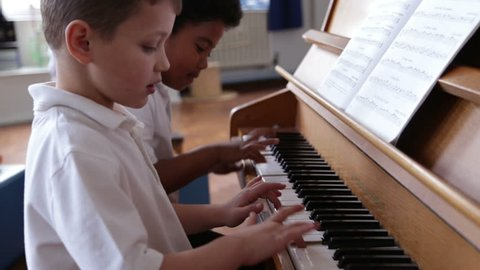 Two Male Students Playing Piano In Music Lesson Together