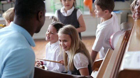 Children With Teacher Playing Instruments In School Band