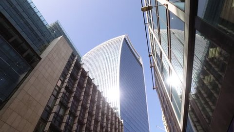 A slow walk through London streets with a stabilised camera towards the large glass Walkie Talkie building with vibrant burning sun and blue sky.