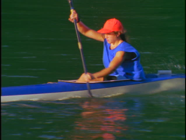 A woman kayaker rows quickly through the water.