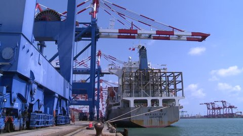 Kaohsiung, Taiwan-10 September, 2015: Gantry cranes loading and unloading trucks at the Container Terminal. Kaohsiung Port in Taiwan encompasses five container terminals.