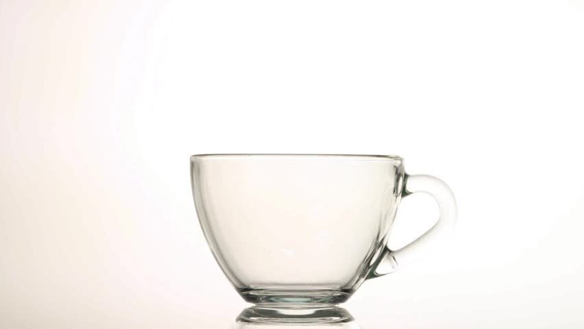 Pouring hot tea into glass cup isolated on white background
