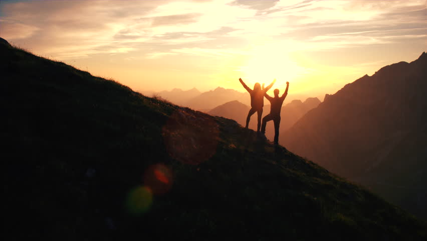Aerial, edited - Rising above hiking couple celebrating successful climb on the mountain with raising arms at beautiful sunset | Shutterstock HD Video #18955649