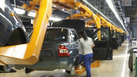 Female worker assembly cars on conveyer