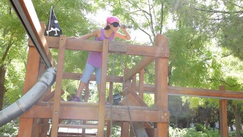 Child girl going up a wooden swing structure in a sunny playground with flare, conquering role playing pirate, playing outdoors. Kids activities and games lifestyle. Girl looking through monocular.
