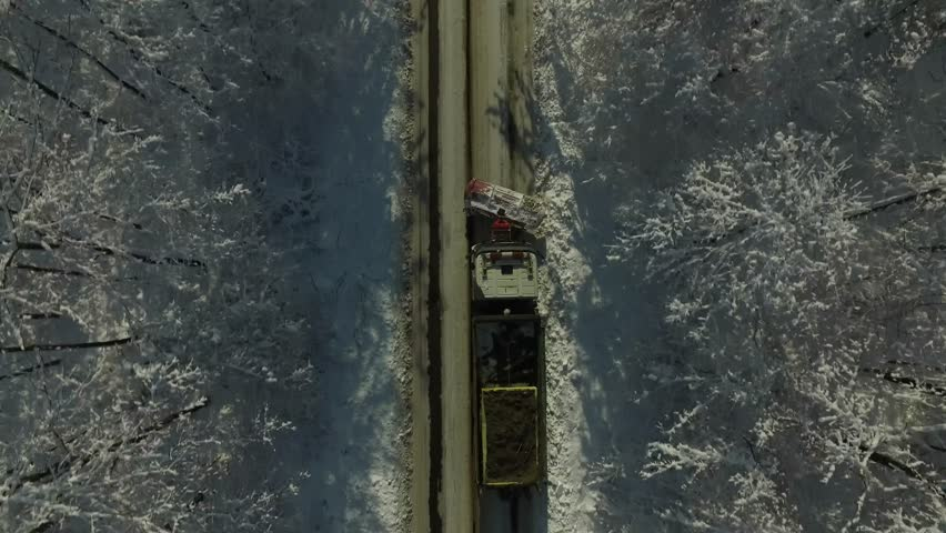4K drone shot of a road passing through the forest in winter