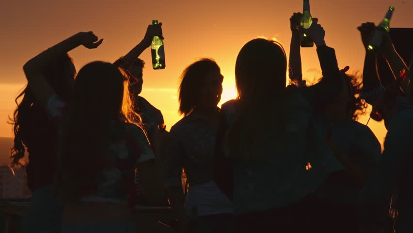 Silhouettes of young people toasting with beer bottles and dancing with raised arms to the music played by dj at rooftop party during beautiful city sunset | Shutterstock HD Video #19079269