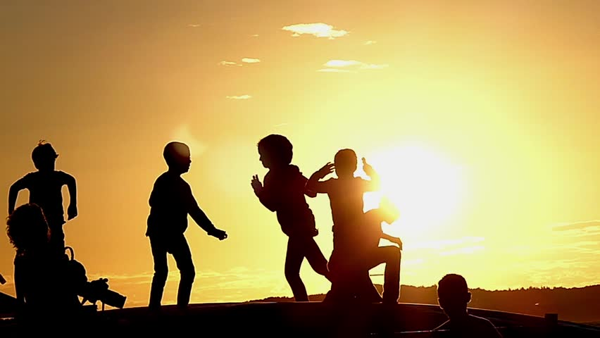 Happy Children Jumping on a Trampoline During Sunset in Slow Motion. Beautiful Action.