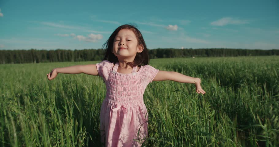 Little Asian girl running in a green field of young wheat,slow motion