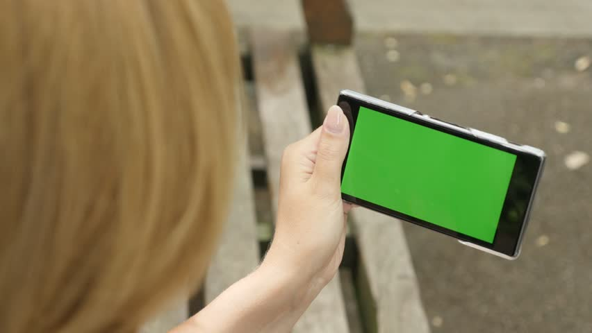 Blond female holding green screen display cellular phone outdoor 4K 2160p 30fps UHD footage - Greenscreen chroma key smart phone blond woman in the park 3840X2160 UltraHD video | Shutterstock HD Video #19105279