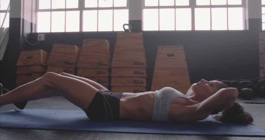 Strong young female athlete on exercise mat doing situps in gym. Fitness woman doing abs crunches. Abs workout routine at the gym.