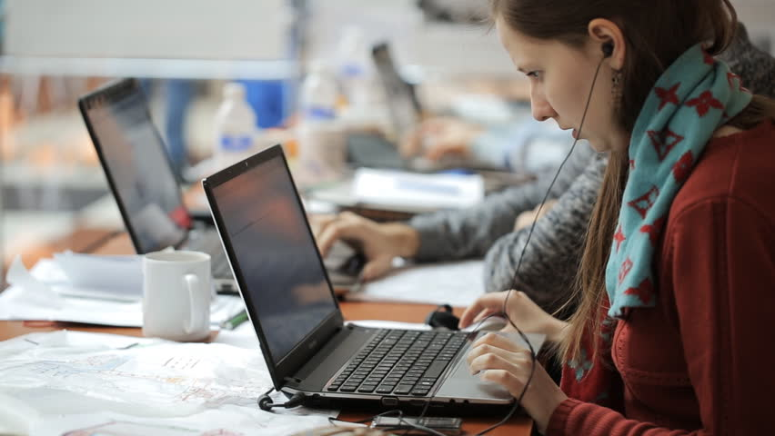 Pretty woman works on laptop in office listening to music.