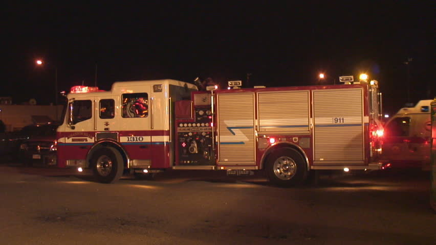 Side view of fire engine parked at night, lights flashing while ambulance arrives behind