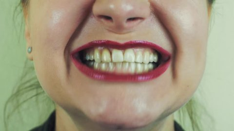 Woman with red pomade show teeth, smile in front camera. Mouth. Face. Make up. Close up
