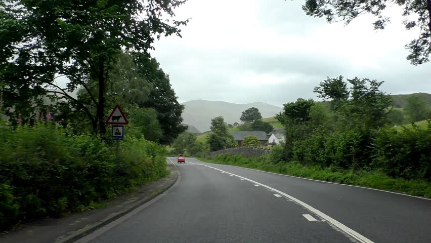 Driving car in English Cumbria countryside through small village.Three wheeled car is being driven in front, windshield view, overcast day