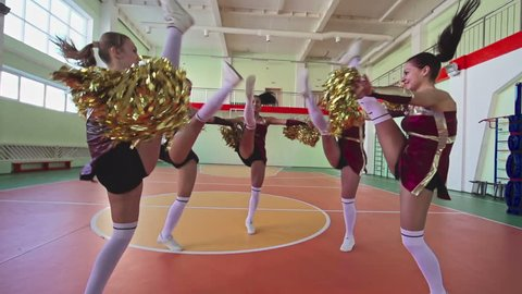 Slow motion shaky camera video, group of beautiful long legged girls jumping in circle facing inwards with pom-poms at cheerleading practice in school gymnasium, low angle