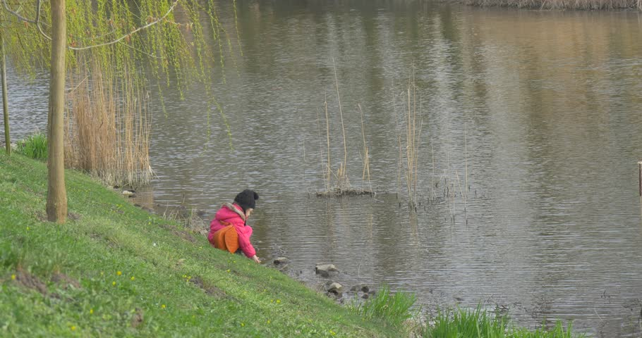 A Little Girl Observes of a Water Flow in the River. She Sits on a Green Grass and Attentively Looks at Water. the Girl Has a Rest in the Centre of Park of a City of Opole (Poland). | Shutterstock HD Video #19176013