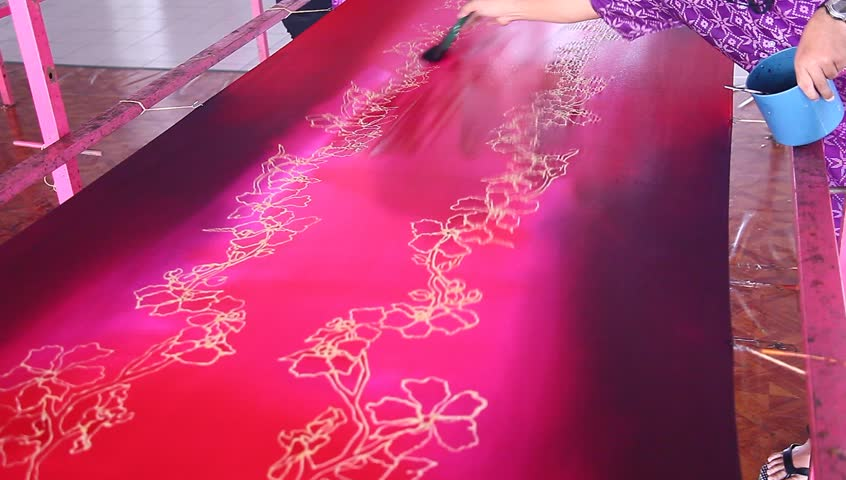 An artist paint a base reddish purple color on beautiful batik fabric with flower motif