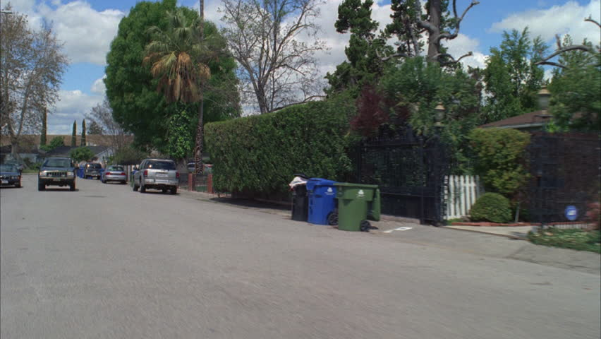 Day Process Plate 45 driver Residential neighborhood, middle class no sidewalks Black SUV following Green bare trees palms Fluffy clouds | Shutterstock HD Video #19233400