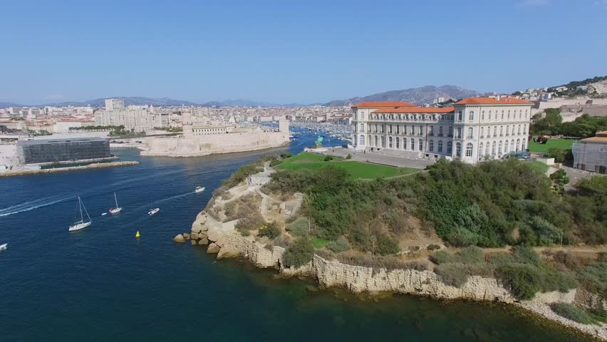 MARSEILLE, FRANCE - JUL 30, 2016: City panorama with vessels sail by Avant port Joliette near edifice of Pharo Palace and Congress Centre and fort Saint-Jean at summer sunny day. Aerial view