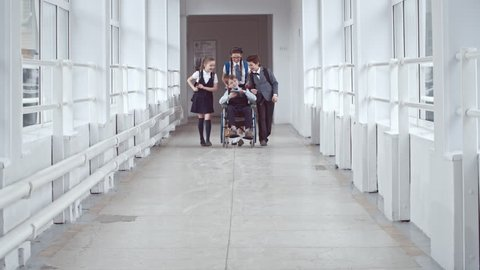 Lockdown of schoolchildren in uniform walking along hallway, girl in glasses pushing paraplegic boy in wheelchair, handicapped schoolboy showing something on tablet laughing and chatting with friends