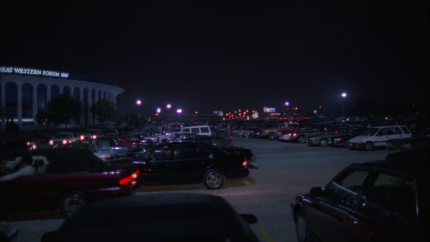 night pan left across full parking lot GREAT WESTERN FORUM arena Los Angeles, cars leaving, House Lakers basketball team from 1967 1999 concert venue