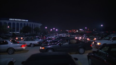 night wide across full parking lot pan left along Great Western Forum LA forum, indoor arena, cars leaving coming House Lakers basketball team from 1967 1999 , concert venue font color red Needs addi