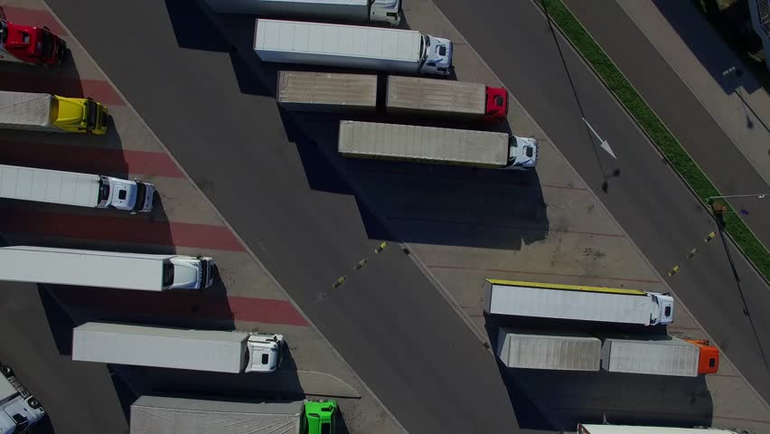 Fly over lorry trucks rows at parking place spot lot aerial top view from above 4K HD. Drivers working hours and rest area. Transportation cargo delivery logistics business vehicles construction