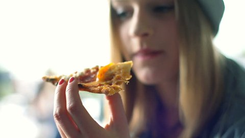 Hipster girl holding slice of pizza and eating it in the restaurant