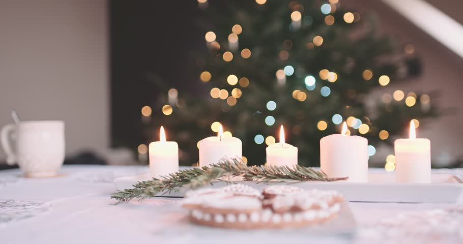 Candles Burning on the Table in front of Abstract Blurred Christmas Lights Bokeh Background. 4K DCi SLOW MOTION 120 fps. Served Dinner Table near Christmas Tree. Winter Holidays Concept. DOLLY SHOT