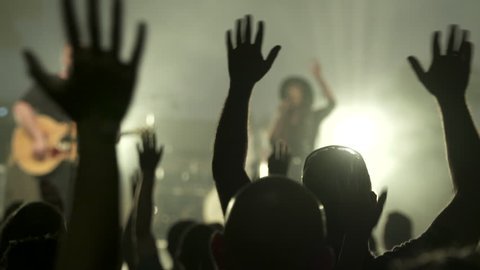 Stock video footage Crowd Raising hands at a concert, focus is on the hands, band is out of focus in background. silhouetted people.