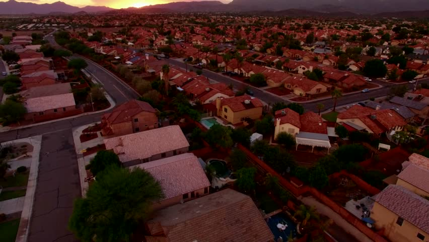 Drone Aerial View of the Sunset over Desert Suburban Homes - Fly Forward Tilt Up Silver Car