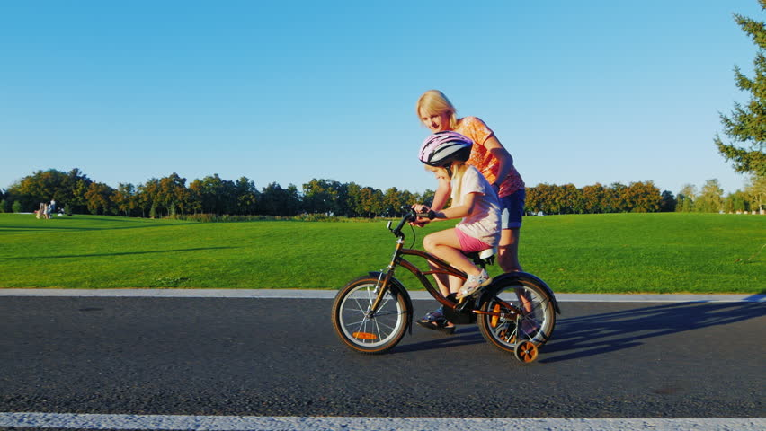 Mom teaches girl to ride a bike. Concept - Help and support for parents, a happy childhood