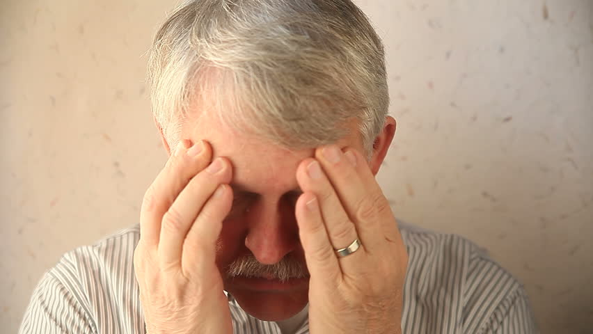 an older man tries to relieve the pain around his eyes
