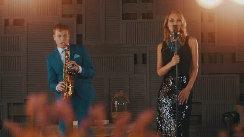 Jazz vocalist in glare dress dance perform with saxophonist in blue suit. Stage. Retro style
