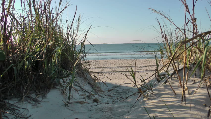 an opening in the sand dune and sea grass leading to a beautiful beach and sea - HD - 1920x1080
