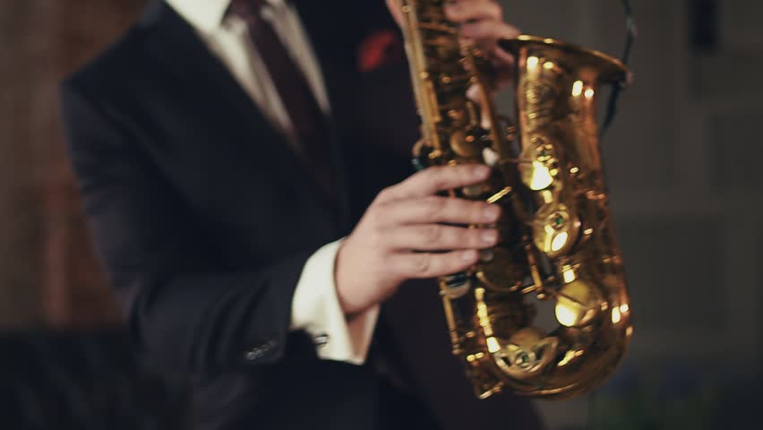 Saxophonist in black suit play jazz on golden saxophone with microphone. Music. Live performance