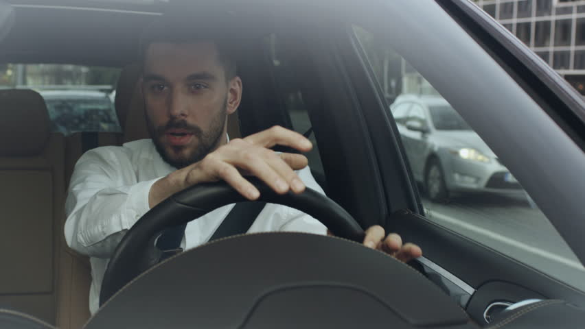 Stressed Businessman Driving a Car. Shot on RED Cinema Camera in 4K (UHD).