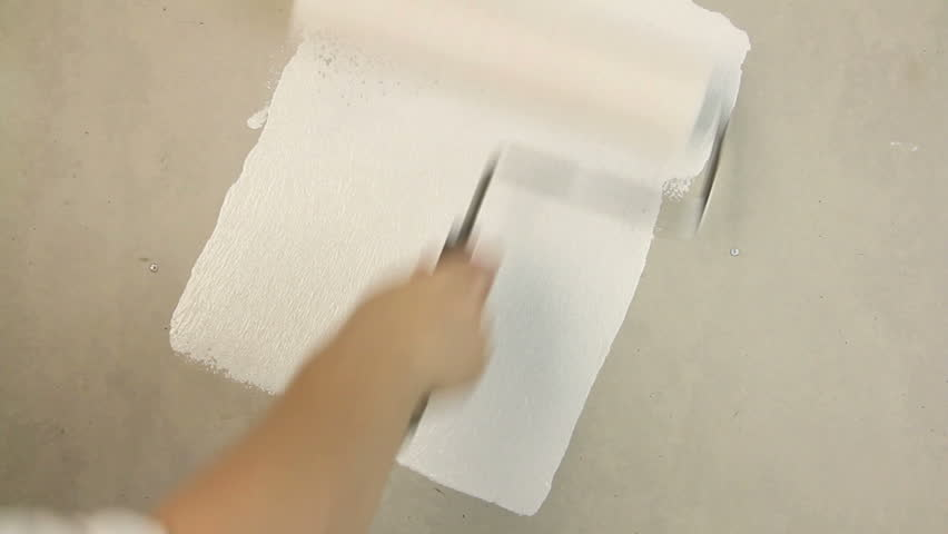Painting out a bare wall with a paint roller with white paint.
