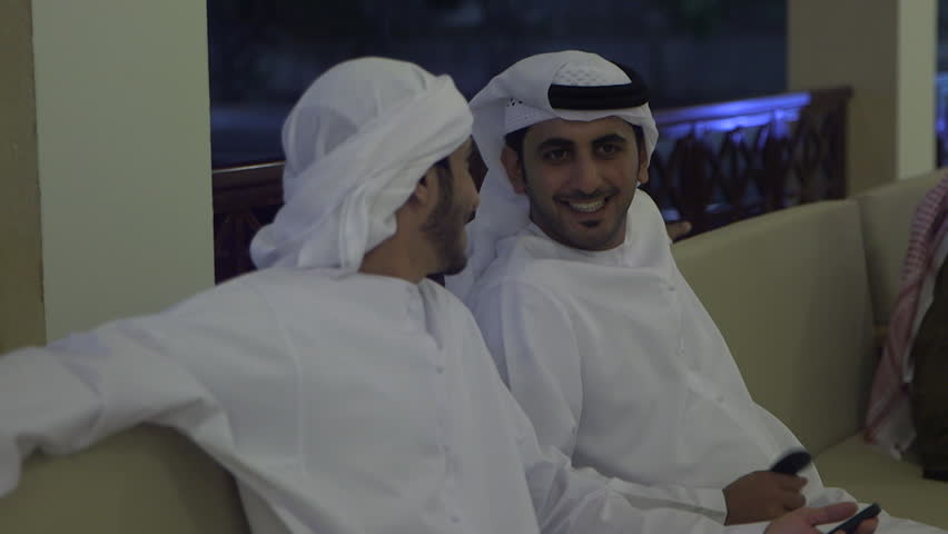 Abu Dhabi, UAE - circa 2013 - CU rack-focus on two Emirati men in white thobes and keffiyehs chatting on the verandah of a caf_ at night. Abu Dhabi, UAE - 2013