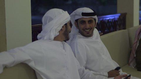 Abu Dhabi, UAE - circa 2013 - CU rack-focus on two Emirati men in white thobes and keffiyehs chatting on the verandah of a caf_ at night. Abu Dhabi, UAE - 2013