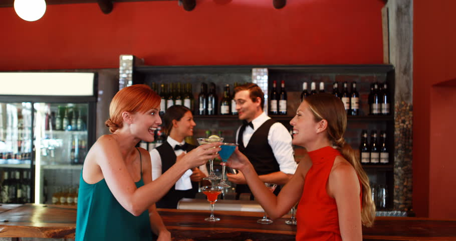 Two women with cocktail drinks talking to each other at counter in bar 4K   Shutterstock HD Video #19525249