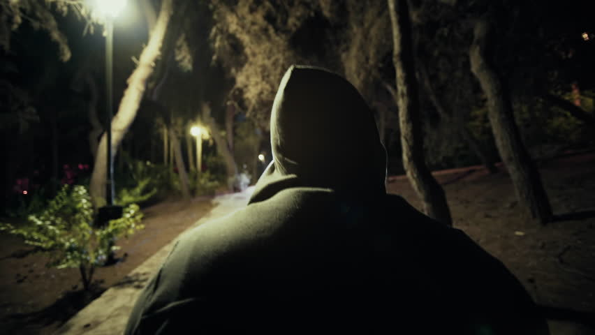 Suspicious hooded figure walks in a dark park at night,gimbal tracking.A suspicious man wearing a hoodie walks in a dark ominous urban park at night